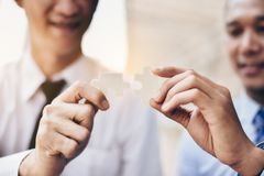 Businessmen hold jigsaw puzzles for each other. Business teamwork concept royalty free stock image