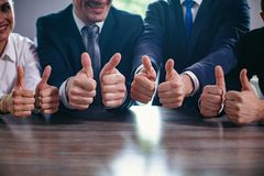 Businessmen holding big thumbs up in a row. Cropped Image Of Businessmen Holding Their Big Thumbs Up While Sitting In A Row. Selective Focus On Business People s stock photo