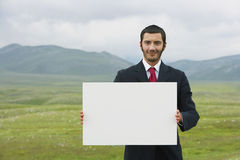 Businessmen Holding Blank Sign In Mountain Field Stock Image