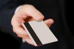 Businessmen holding credit card proposing it to you. Hand in bla Stock Photos