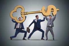 The businessmen holding giant key in finance concept. Businessmen holding giant key in finance concept Stock Photo