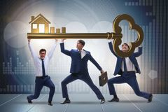The businessmen holding giant key in real estate concept. Businessmen holding giant key in real estate concept Stock Image