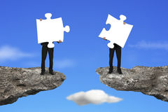 Businessmen holding jigsaw puzzles to connect on cliff with sky Royalty Free Stock Photography