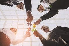 Businessmen Holding and Putting Puzzle Pieces. Together. Teamwork and Cooperation Concept. Bottom View. Four Smart Cute Business Partners in Office stock photos