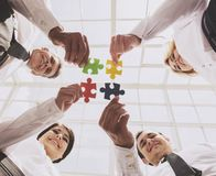 Businessmen Holding and Putting Puzzle Pieces Royalty Free Stock Image