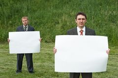 Businessmen holding sheet of paper Royalty Free Stock Image