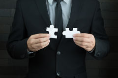 Businessmen holding two jigsaw to connect Stock Photos