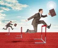 Businessmen hopping over treadmill barrier Royalty Free Stock Photography