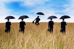 Businessmen insurance agent. On the meadow with umbrella Stock Photos