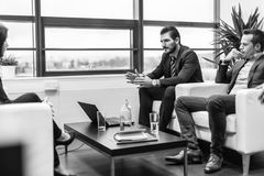 Businessmen interviewing female candidate for job in modern corporate office. Stock Photography