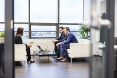Businessmen interviewing female candidate for job in modern corporate office. Stock Images