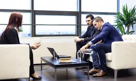 Businessmen interviewing female candidate for job in modern corporate office. Royalty Free Stock Photography