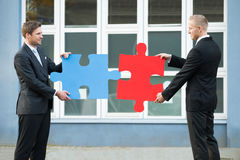Businessmen Joining Jigsaw Pieces Outside Office Royalty Free Stock Photos