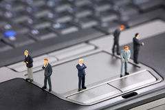 Businessmen on a laptop. Group of miniature businessmen standing on a laptop. Modern business concept Royalty Free Stock Photo