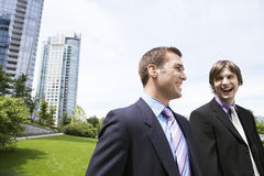 Businessmen Laughing By Office Buildings. Two cheerful young businessmen laughing near office buildings Royalty Free Stock Photo