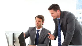 Businessmen looking at computer screen talking stock footage