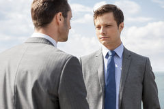 Businessmen looking at each other against sky royalty free stock photography