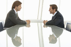 Businessmen Looking At Each Other In Conference Room. Side view of businessmen looking at each other in conference room royalty free stock photo
