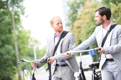 Businessmen looking at each other while holding bicycles outdoors Royalty Free Stock Photography