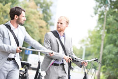 Businessmen looking at each other while holding bicycles outdoors Royalty Free Stock Photo
