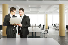 Businessmen looking at laptop in modern loft style office Stock Photography