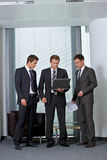 Businessmen looking at laptop in office Stock Photography