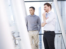 Businessmen looking out of window Stock Images