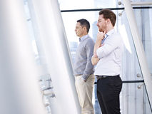 Businessmen looking out of window Stock Image