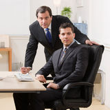 Businessmen looking serious at desk in office. Confident businessmen looking serious at desk in office Royalty Free Stock Photos