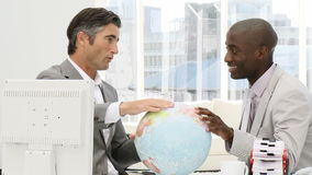 Businessmen looking at a terrestrial globe. In the office stock footage