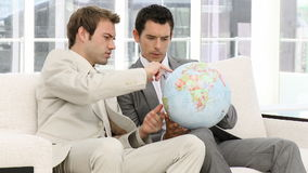 Businessmen looking at a terrestrial globe. Sitting on a sofa stock video footage