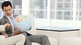Businessmen looking at a terrestrial globe. Sitting on a sofa stock footage