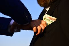 Businessmen make bargain. Male hand puts cash into suit pocket. Businessmen make bargain. Male hand puts cash as bribery into mans suit pocket on blue background royalty free stock photo