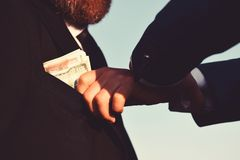 Businessmen make bargain. Male hand puts cash into suit pocket. Businessmen make bargain. Male hand puts cash as bribery into mans suit pocket on blue background stock photo