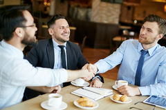 Businessmen Making a Deal. Two formally dressed pleased businessmen in shirts on casual meeting in cafe sharing coffee and shaking hands in agreement over deal royalty free stock image