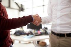 Businessmen making handshake at office Stock Photography