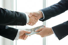 Businessmen making handshake while passing money Stock Images