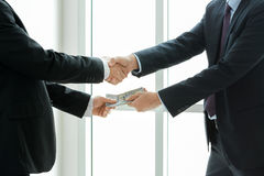 Businessmen making handshake while passing money Royalty Free Stock Photography