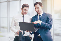 Businessmen making project with a laptop. Get ready. Handsome cheerful successful businessmen making project and using a laptop while working in an office Royalty Free Stock Image