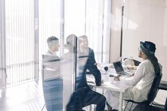 Businessmen in meeting room View through glass. Business and entrepreneurship. Multi-ethnic group of business partners of various ages and ethnicities gathered royalty free stock image