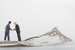 Businessmen miniatures and money Stock Image