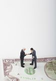 Businessmen miniatures and money Stock Images