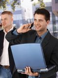 Businessmen on mobile phone outside of office Stock Photo