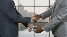 Businessmen with money shake hands.