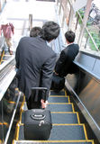 Businessmen on moving staircase stock photography