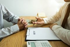 Businessmen offer home rental contracts to customers.Business re stock photo