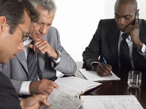 Businessmen With Paperwork At Conference Table Stock Photography