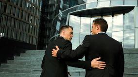 Businessmen pat on the shoulder and talking. Slow motion. Colleagues and friends. Two cheerful businessmen pat on the shoulder and talking to each other while stock footage