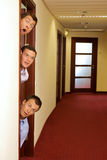 Businessmen peeking out of door Stock Photo