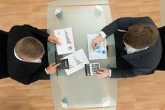 Businessmen with pen and calculator analyzing graph Royalty Free Stock Photo